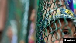سری نگر میں پابندیوں کے دوران ایک بچہ باڑ کے پار سے جھانک رہا ہے۔ 16 اگست