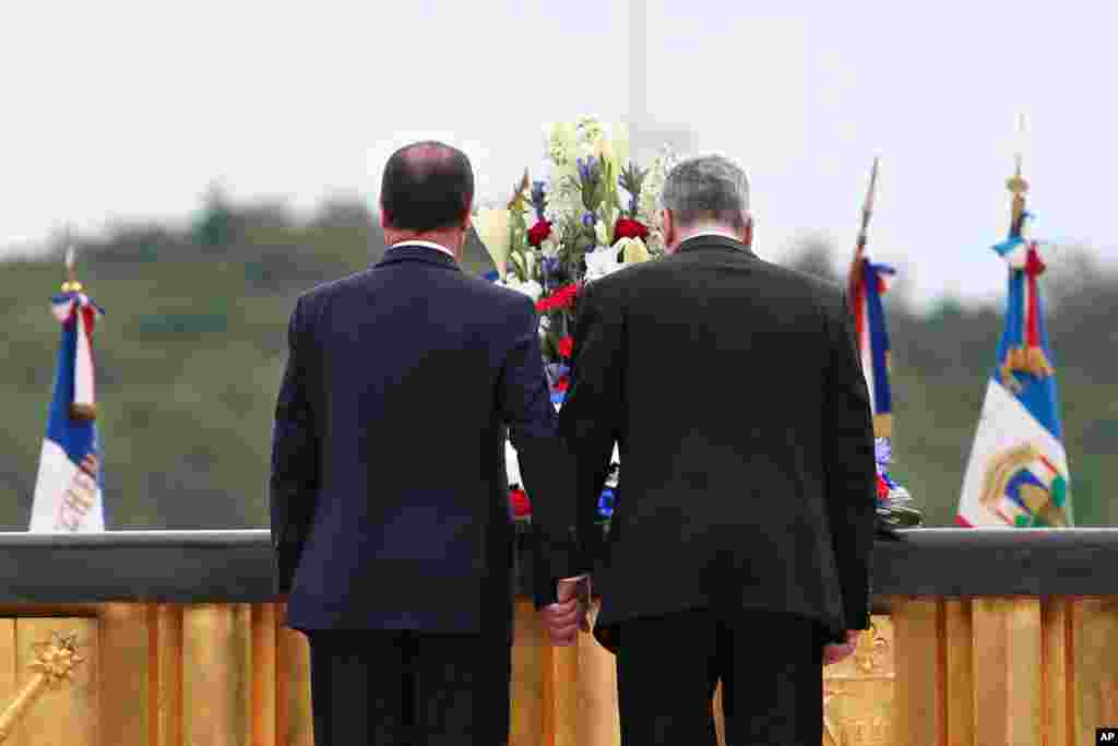 French President Francois Hollande (left) and German President Joachim Gauck pay their respects during a ceremony to mark the 100th anniversary of the outbreak of World War I, at the National Monument of Hartmannswillerkop, in Wattwiller, eastern France, Aug. 3, 2014.