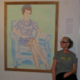 Judy Byron sits next to the painting of herself as a young girl