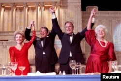 President Ronald Reagan (2nd L) and Vice President George Bush, (2nd R), accompanied by wives Nancy (L) and Barbara, join hands after the President endorses Bushes run for the Presidency