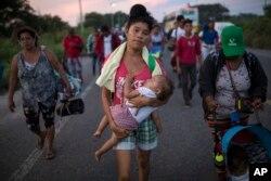 Dvadeset-dvogodišnja Maria Gomes nosi jednogodišnjeg sina Davida Moisesa, u kravanu migranata iz Centralne Amerike, koji je trenurno blizu Jučitana, u Mekisku (Foto: AP)