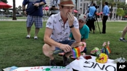 Johnathan Dalton breaks down as he places flowers on a makeshift memorial, Monday, June 13, 2016 in memory of two of his friends who were killed during a fatal shooting at the Pulse Orlando nightclub in Orlando, Fla. (AP Photo/Chris O'Meara)