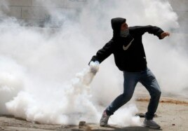 A Palestininan throws back a tear gas cannister during clashes on Nakba Day near Hebron.