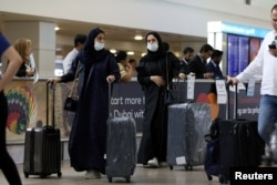 Travelers wear masks as they arrive at the Dubai International Airport