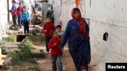 FILE - Syrian refugees walk in an informal settlement in Zahle in the Bekaa Valley, Lebanon, Oct. 16, 2014.