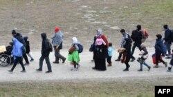 Les migrants se rendent au premier point d'enregistrement de la police fédérale allemande après avoir franchi le pont frontalier germano-autrichien du sud de l'Allemagne, le 27 octobre 2015.