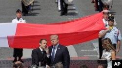 Nan selebrasyon Priz La Bastille nan Chan Zelize a Pari, Prezidan Fransè a, Emmanuel Macron, agoch, kanpe ansanm ak tokay ameriken li, Prezidan Donald Trump, a dwat. 14 jiyè 2017.