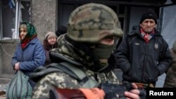 Local residents wait for a bus to flee the conflict in Debaltseve, eastern Ukraine, Feb. 5, 2015.