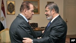 Caretaker Prime Minister Kamal el-Ganzouri, left, shakes hands with newly elected President Mohamed Morsi in Cairo, June 25, 2012. (photo released by Middle East News Agency)