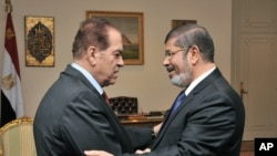 Predsjednik Morsi se rukuje s vršiteljem dužnosti premijera Kamal el-Ganzourijem