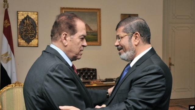 PM sementara Mesir, Kamal el-Ganzouri (kiri) memberikan selamat kepada Presiden terpilih Mohamed Morsi di Kairo, Senin (25/6).