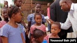 Children in Conakry, Guinea, return to school - and a daily temperature check.
