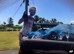 """Genshu Price berdiri di belakang truk setelah memuatnya dengan kaleng dan botol daur ulang dari Kualoa Ranch di Kāne'ohe, Hawaii, untuk penggalangan dana """"Bottles4College"""", Mei 2021. (Maria PRice/ Bottles4College via AP)"""