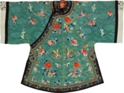 A woman's coat from 19th century China. The Textile Museum says the green color and flowers on this coat represent the wearer's wish for fertility.