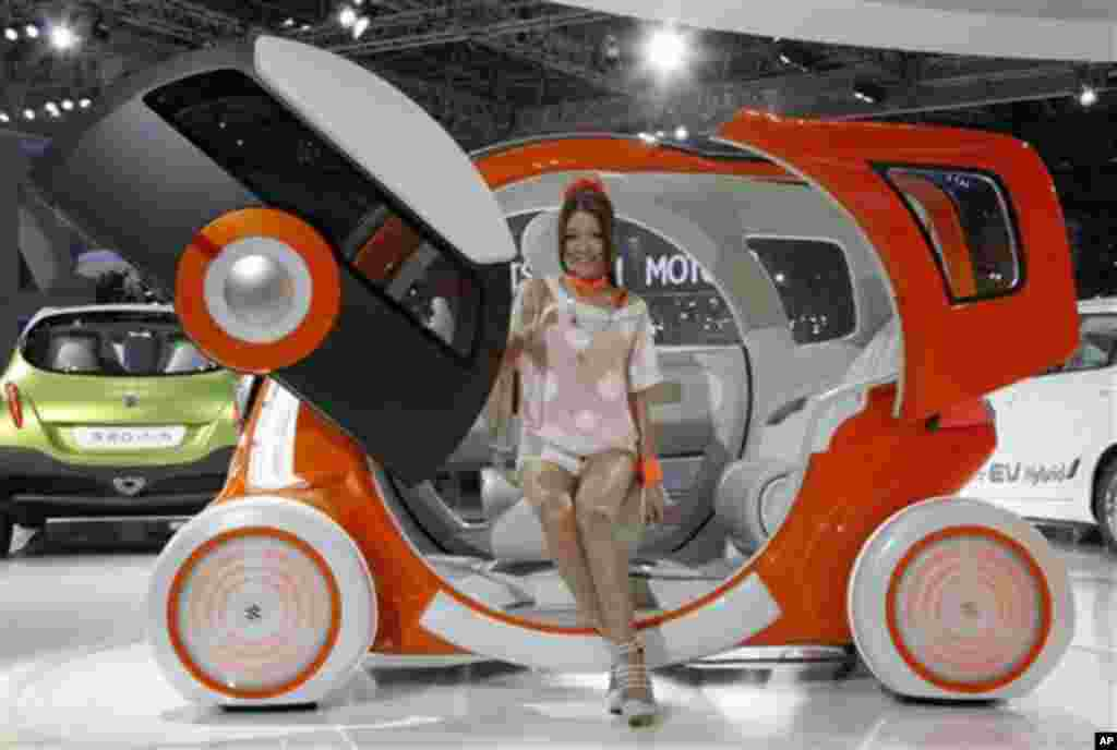 "A model sits on Suzuki Motor Corp.,'s concept car ""Q-Concept"" during the press preview of Tokyo Motor Show in Tokyo, Wednesday, Nov. 30, 2011. The Tokyo Motor Show opens to the public this weekend. (AP Photo/Koji Sasahara)"