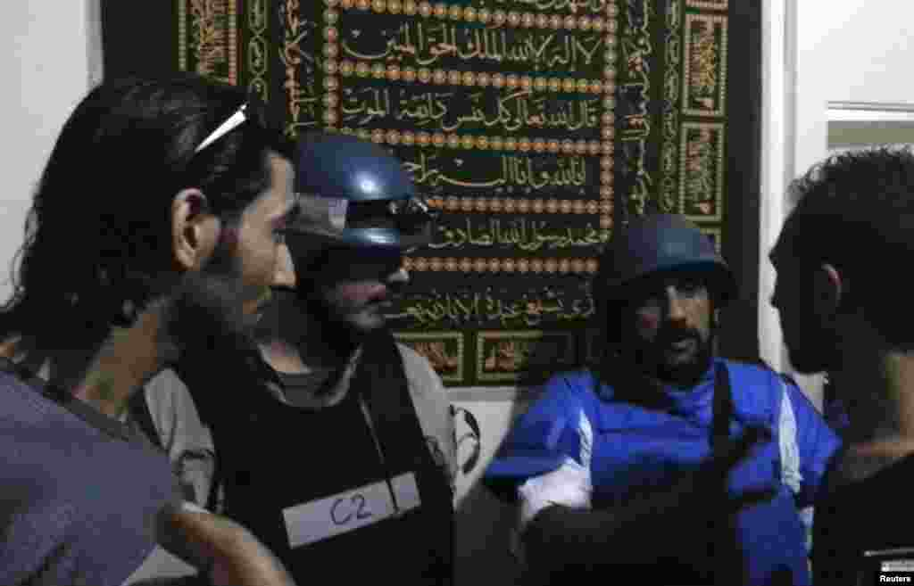 U.N. chemical weapons experts meet residents at one of the sites of an alleged poison gas attack in a southwestern Damascus suburb, August 26, 2013.