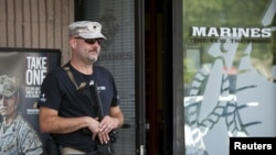 U.S. Army veteran Chris Murphy, armed with a rifle and handgun, stands near a U.S. Marines recruiting office in Everett, Washington July 23, 2015. According to the U.S. Army, citizens across the U.S. volunteered to station themselves near military recruiting centers to offer protection after the 2015 shooting in Chattanooga, Tennessee.