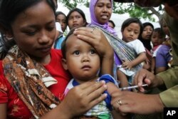 FILE - An Indonesian child receives a shot of measles vaccine in Banyusoco village near Gunung Kidul, Indonesia.