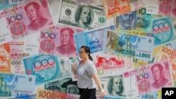 中國星期天(9月1日)表示,將加大宏觀經濟政策的逆週期調節力度,實施好穩健貨幣政策。圖為一女士行經外幣找換店。