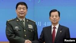 2015年2月4日首尔: 中国国防部长常万全(左)与韩国外长韩民求(右)握手
