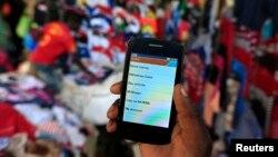 Seorang pria menunjukkan layar ponselnya yang memperlihatkan aplikasi transaksi keuangan di pasar di Kibera, Nairobi di Kenya.