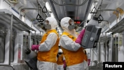 Employees from a disinfection service company sanitize a subway car depot amid coronavirus fears in Seoul, South Korea, March 11, 2020.