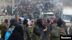 Tentara pemberontak dan warga sipil berkumpul, menunggu evakuasi dari Aleppo, Suriah (16/12). (Reuters/Abdalrhman Ismail)