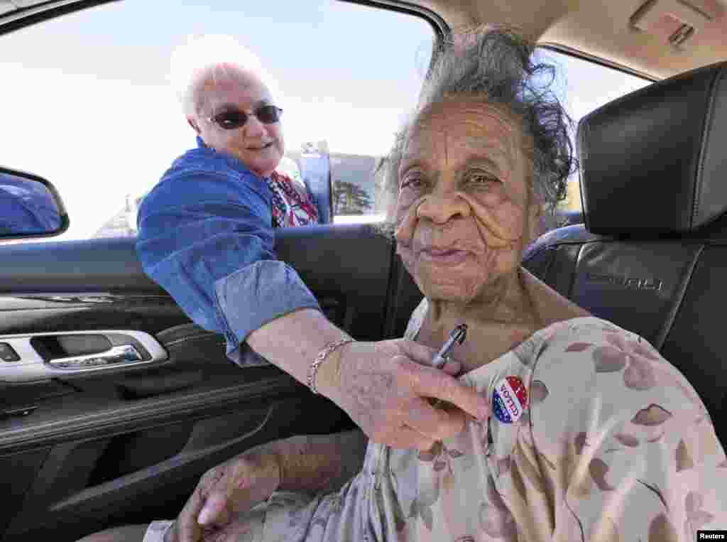 """Grace Bell Hardison, de 100 anos de idade, recebe um autocolante """"Votei Hoje"""" depois de votar a partir do seu carro em Belhaven, no estado da Carolina do Norte."""