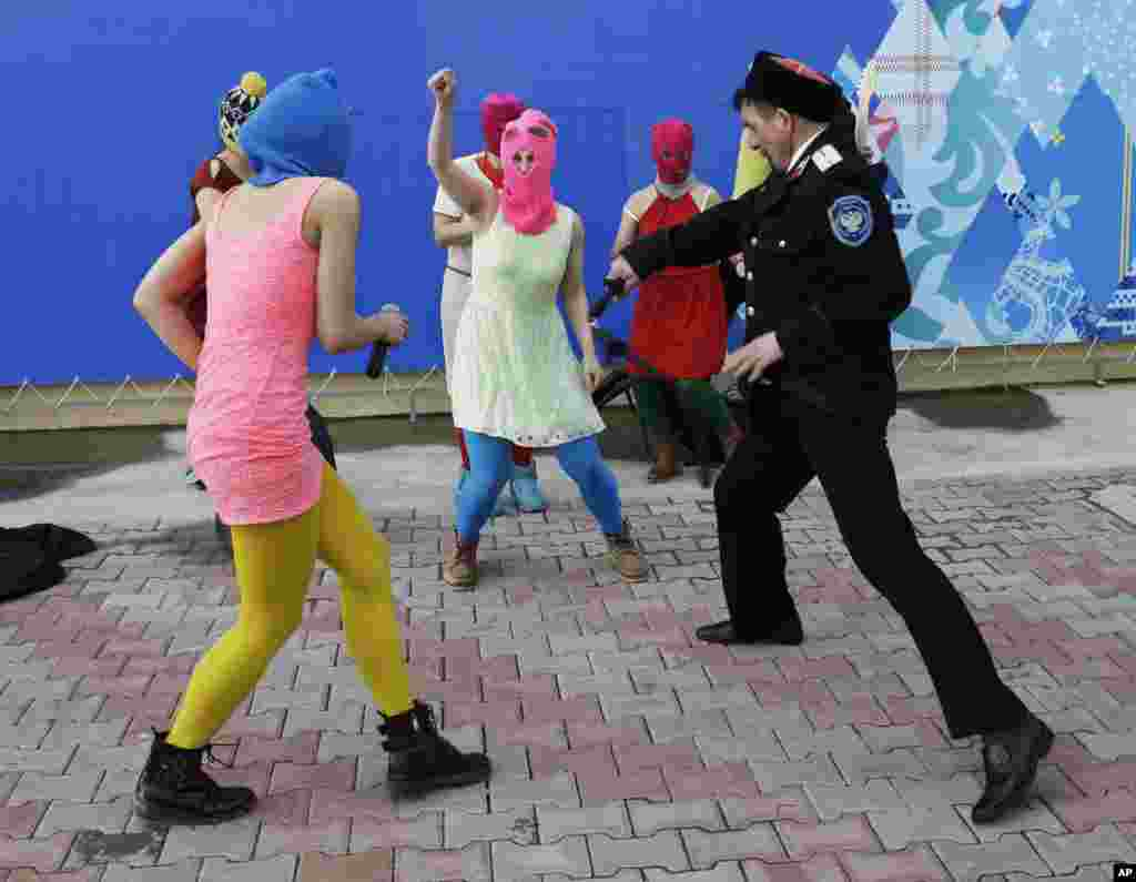 Members of the punk group Pussy Riot, including Nadezhda Tolokonnikova in the blue balaclava and Maria Alekhina in the pink balaclava, are attacked by Cossack militia in Sochi, Russia, Feb. 19, 2014.
