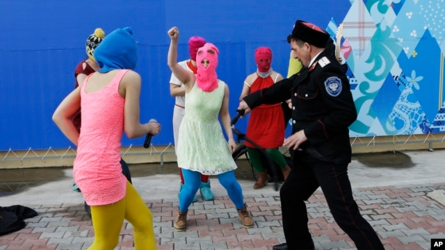 Members of the punk group Pussy Riot, including Nadezhda Tolokonnikova in the blue balaclava and Maria Alekhina in the pink balaclava, are attacked by Cossack militia in Sochi, Russia, on Feb. 19, 2014.