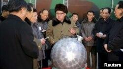 김정은 북한 국무위원장이 핵무기 연구 부문 과학자, 기술자들을 만나 핵무기 병기화 사업을 지도하는 모습을 지난 3월 조선중앙통신이 보도했다. 사진 아래쪽에 핵탄두 기폭장치 추정 물체가 보인다.