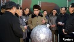 김정은 북한 국방위원회 제1위원장이 핵무기 연구 부문 과학자, 기술자들을 만나 핵무기 병기화 사업을 지도하는 모습을 지난달 9일 조선중앙통신이 보도했다. 사진 아래쪽에 핵탄두 기폭장치 추정 물체가 보인다. (자료사진)