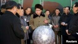 김정은 북한 국방위원회 제1위원장이 핵무기 연구 부문 과학자, 기술자들을 만나 핵무기 병기화 사업을 지도하는 모습을 지난 9일 조선중앙통신이 보도했다. 사진 아래쪽에 핵탄두 기폭장치 추정 물체가 보인다. (자료사진)