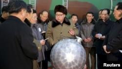 북한의 김정은 노동당 위원장이 핵무기 연구 부문 과학자, 기술자들을 만나 핵무기 병기화 사업을 지도하는 모습을 지난 3월 조선중앙통신이 보도했다. 사진 아래쪽에 핵탄두 기폭장치 추정 물체가 보인다. (자료사진)