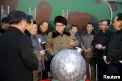 김정은 북한 국방위원회 제1위원장이 핵무기 연구 부문 과학자, 기술자들을 만나 핵무기 병기화 사업을 지도하는 모습을 조선중앙통신이 지난 3월 보도했다. 사진 아래쪽에 핵탄두 기폭장치 추정 물체가 보인다.