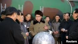 金正恩和科學家圍在一個小型銀色球體旁