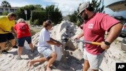 Walker Townsend (derecha), de Isle of Palms, Carolina del Sur, llena un saco de arena que sostiene Dalton Trout, en un estacionamiento municipal donde se reparte arena de forma gratuita dentro de los preparativos para la llegada del huracán Florence a la región, el 10 de septiembre de 2018. (AP Foto/Mic Smith)