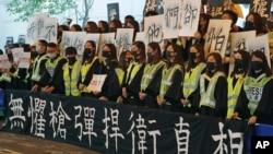 香港中文大学毕业生在2019年11月7日的毕业典礼上戴口罩手举标语横幅抗议。