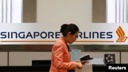 FILE - A staff member walks by a Singapore Airlines (SIA) logo at a ticketing counter at Changi airport in Singapore.