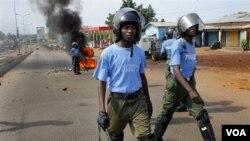 Aparat keamanan Guinea berpatroli di Conakry. Demonstran membakar ban-ban di jalanan, seperti terlihat di latar belakang foto ini.
