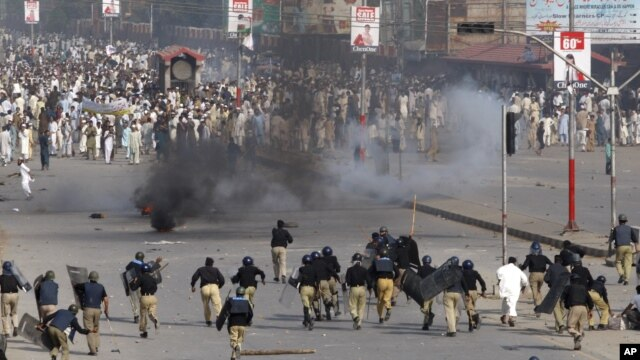 Police chase protesters during an anti-U.S. rally in Peshawar, Pakistan, September 21, 2012.