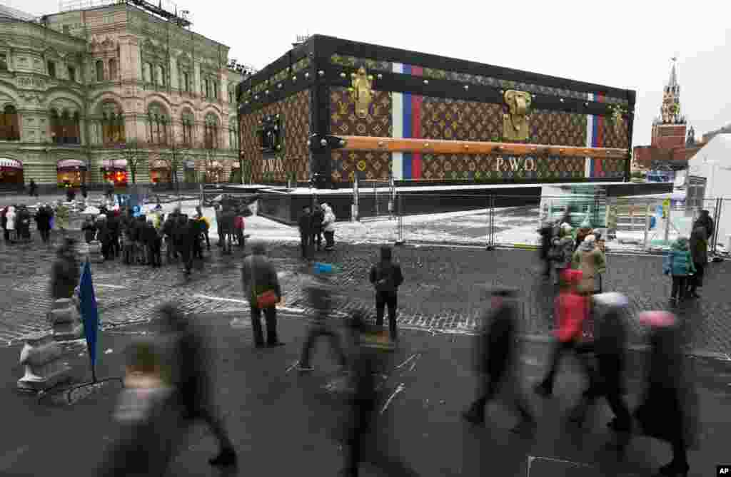 Tourists and visitors pass by a two-story Louis Vuitton suitcase erected at the Red Square in Moscow, Russia. Politicians didn't like it, the public didn't like it, so the gigantic Louis Vuitton suitcase is being booted out of Red Square. The GUM department store on Red Square, which is responsible for 30-feet (nine meters) high and 100-feet (30-meters) long construction, promised in a statement that it would be dismantled.