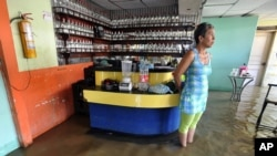 FILE - A woman stands in a flooded disco in Juanchito, Colombia, Dec. 7, 2011.