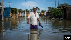 "FILE - A local resident wades through water on a street in the ""El Indio"" settlement on the outskirts of Piura, in northern Peru, March 23, 2017."