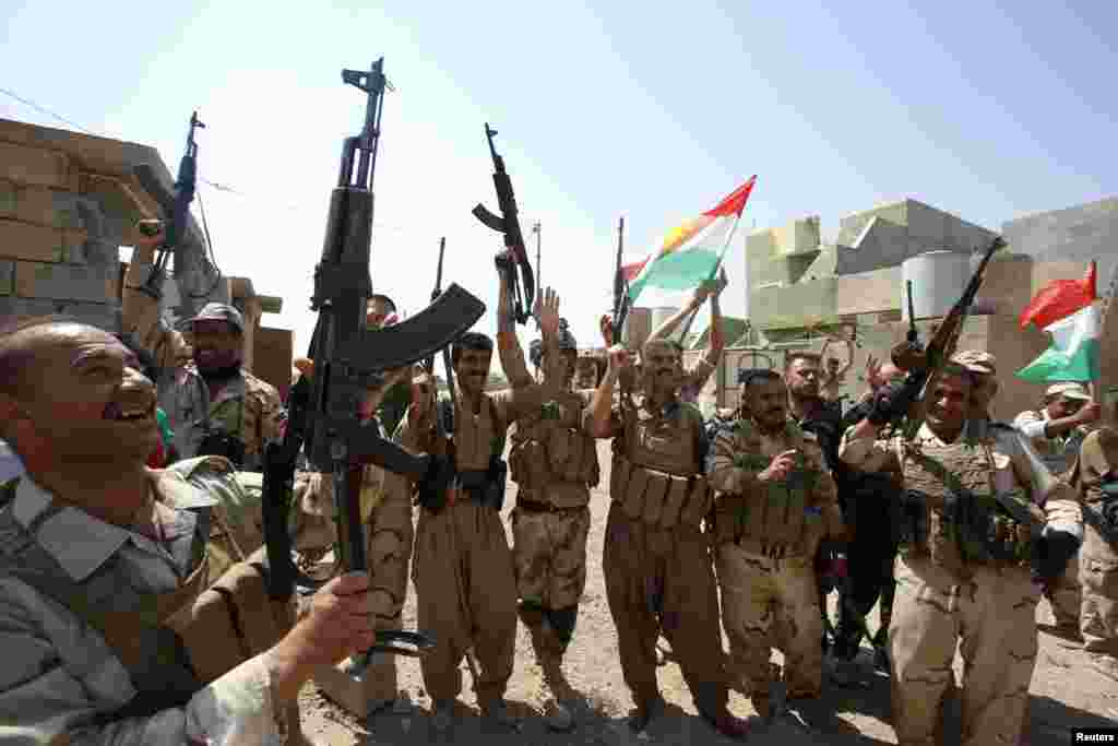 Kurdish peshmerga forces celebrate taking control of Sulaiman Bek from the Islamic State militants, in the northwest of Tikrit city, Sept. 1, 2014.
