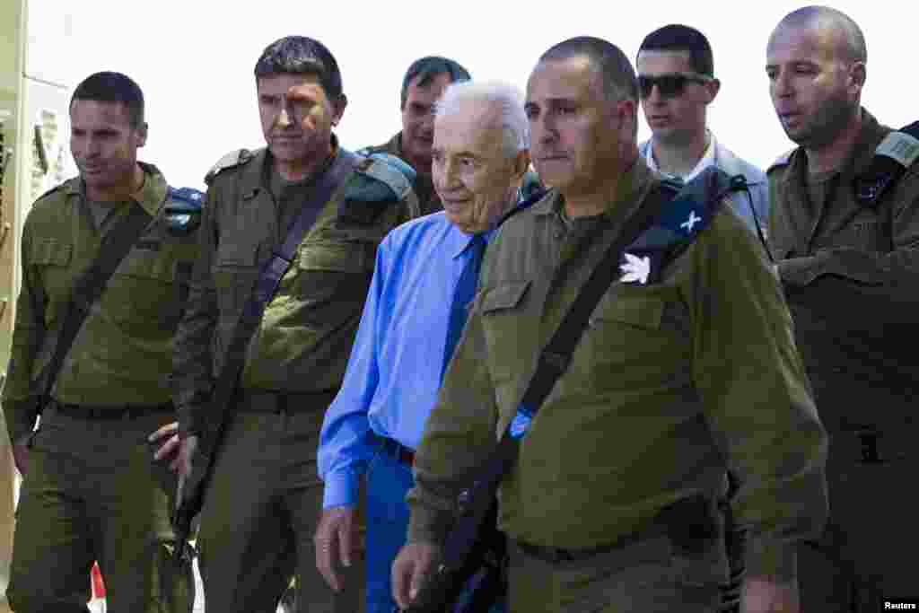 Israel's President Shimon Peres (center) walks with Israeli military commanders during a visit to the site of an Iron Dome anti-missile shield, near the southern city of Ashkelon, July 17, 2014.