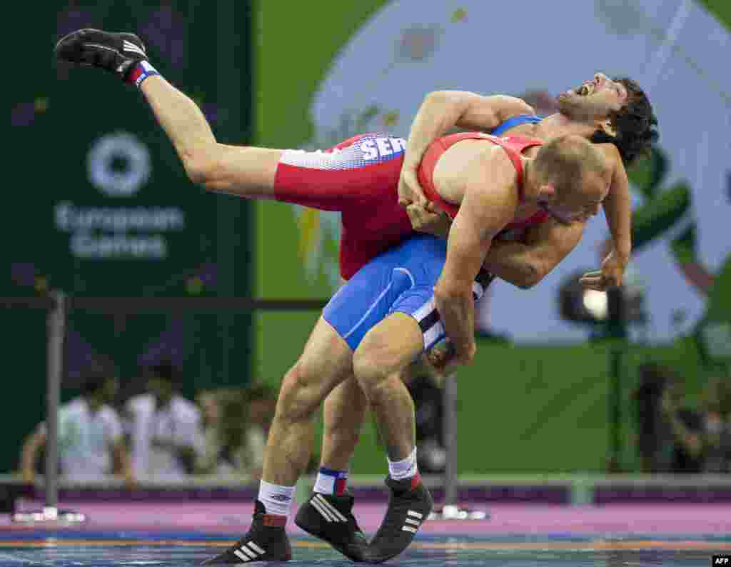 Azerbaijan's Hassan Aliyev (R) wrestles with Serbia's Aleksander Maksimovic during their men's Greco-Roman 66kg wrestling Bronze medal event at the 2015 European Games in Baku, Azerbaijan.