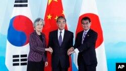 21일 강경화 한국 외교부 장관(왼쪽부터)과 왕이 중국 외교담당 국무위원 겸 외교부장, 고노 다로 일본 외무상이 베이징 구베이수이전에서 열린 '제9차 한·중·일 외교장관 회의'에서 만나 악수하고 있다.