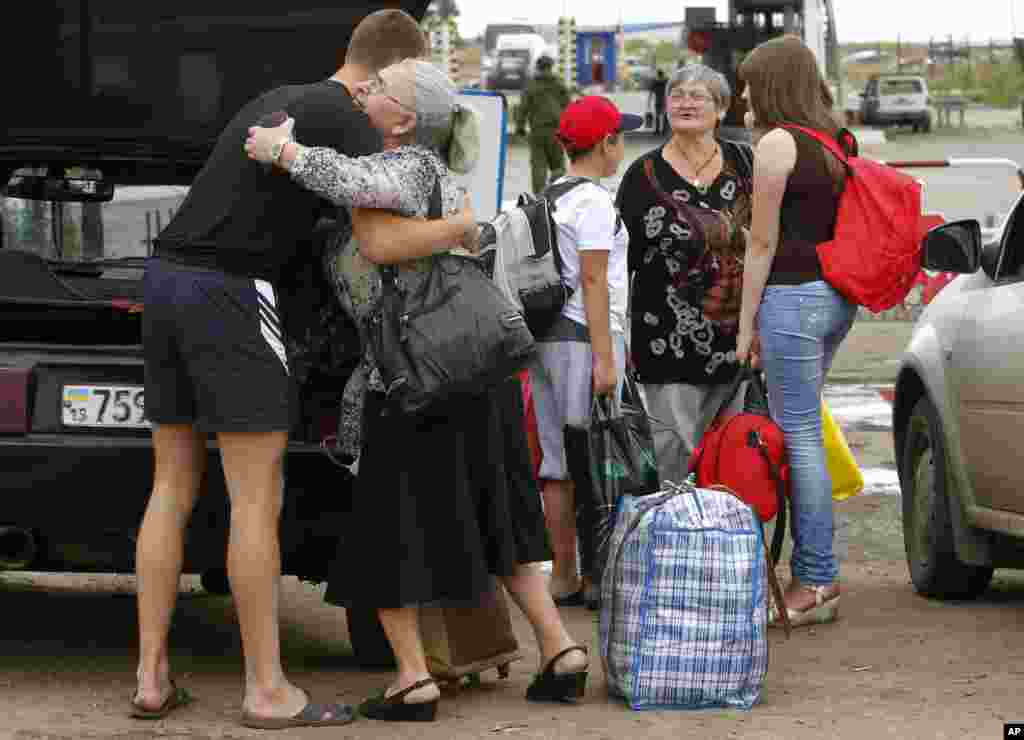 A man says goodbye to his relatives as they prepare to cross the border into Russia at the checkpoint in Izvaryne, Luhansk region, eastern Ukraine, June 26, 2014.