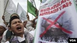 Demonstran anti-Ahmadiyah mengusung poster bergambar Mirza Ghulam Ahmad yang wajahnya dicoreng dalam sebuah aksi protes di Jakarta, Selasa (1/3).